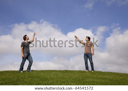 two young teenager pointing to the copy space between the two - stock photo