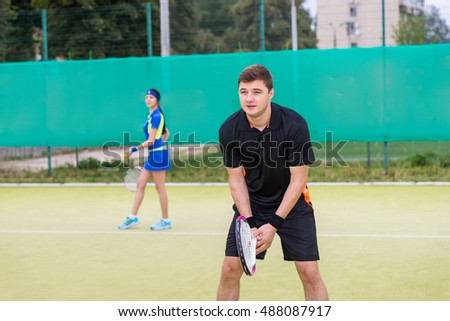 Two young tennis players wearing a sportswear playing doubles at tennis court at early morning