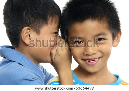 Two young toddler boys telling a secret; one boy is laughing - stock photo