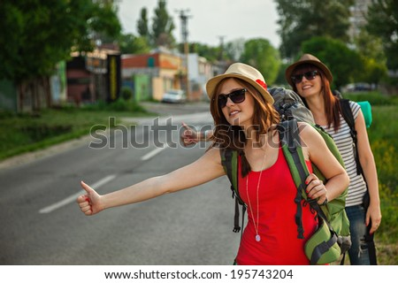 Two Young Tourist Girls Hitchhiking On The Road - stock photo