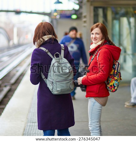 Two young tourist in Parisian subway, looking for the train on the platform