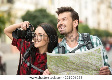 Two young tourists with backpacks, touristic map and camera. Sightseeing City. - stock photo