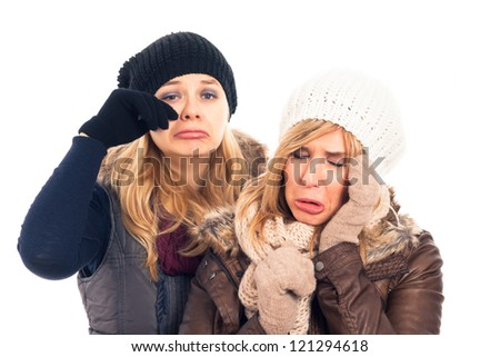 Two young unhappy sad women in winter clothes, isolated on white background.