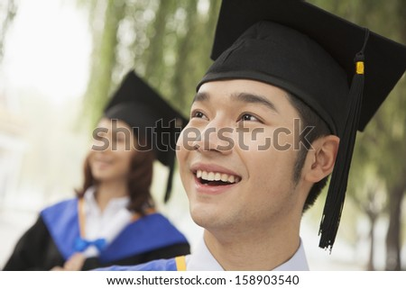 Two young university graduates looking away