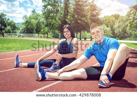 Two young vital people doing stretching relaxing exercises on athletics running track with positive facial expression. - stock photo