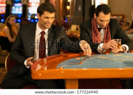 Two young well-dressed men behind gambling table in a casino - stock photo
