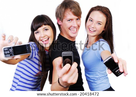 Two young woman and a man between them. They're showing mobile phones' screen. Isolated on white in studio.