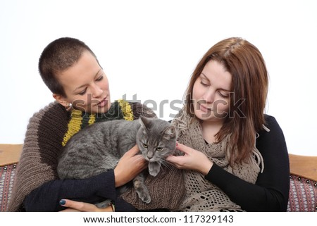 Two young woman and gray domestic cat at sofa