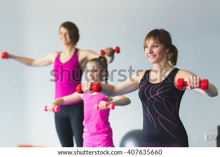 Two young woman and little girl doing gymnastic exercises