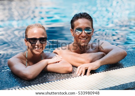 Two young woman and man smiling broadly at the camera as they stand in the pool