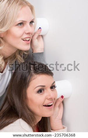 Two young woman are using a glass as telephone listening to conversation, gossip through the wall. - stock photo