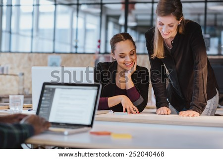 Two young woman at office working on a new creative design. Diverse team of professionals looking at a document smiling. - stock photo