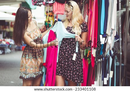 two young woman buying clothes at the city mall - stock photo