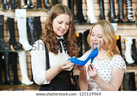 two Young woman choosing shoes during footwear shopping at shoe shop - stock photo