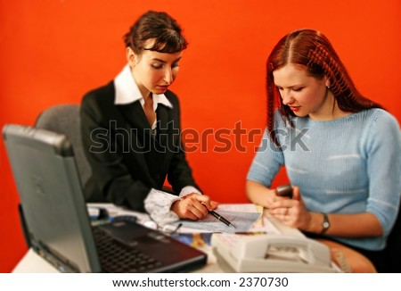 two young woman discuss over a blueprint -isolated