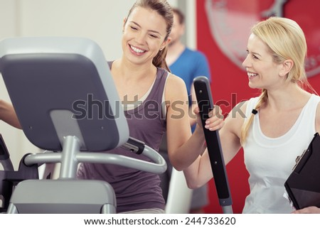 Two young woman enjoying their exercise routine at the gym laughing and smiling as they watch the digital readout on the machine in a healthy lifestyle concept