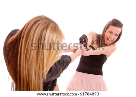 Two young woman fighting for a shoe over a white background - stock photo
