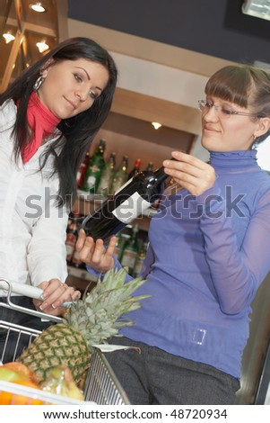 Two young woman looking vine bottle in shop