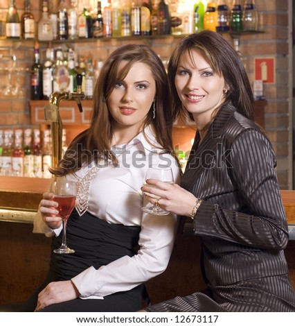 two young woman near a bar drinking and chatting each others