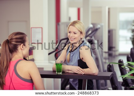 Two young woman relaxing over drinks at the gym enjoying a healthy energy drink after their workout in a health and fitness concept