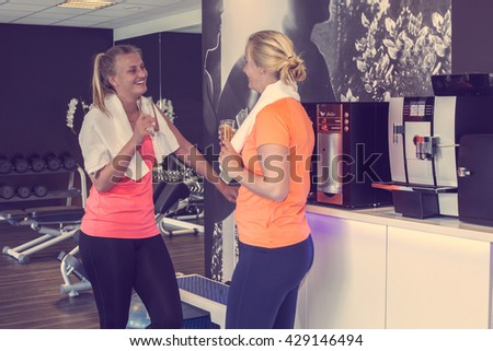 Two young woman relaxing over drinks at the gym enjoying a healthy energy drink after their workout in a health and fitness club