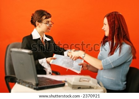 two young woman shake hands in work environment