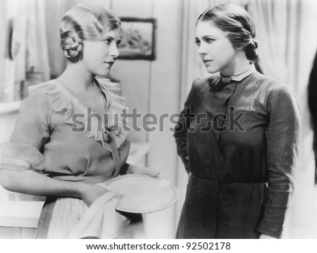 Two young woman talking with each other while doing the dishes - stock photo