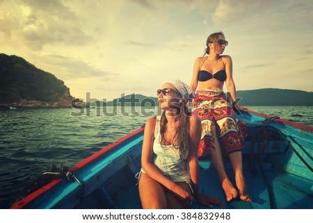 Two young woman traveling by boat at sunset among the islands - stock photo