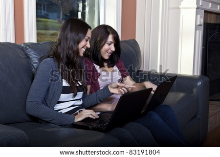 Two Young woman using laptops