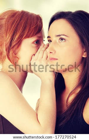 Two young womans talking gossip