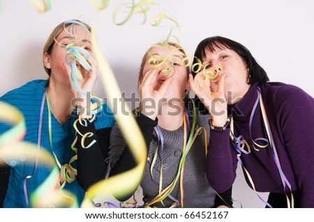 Two young women and one senior woman celebrating New year's eve. Shot taken in front of white background