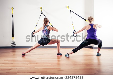 Two young women are doing bodyweight exercises with straps - stock photo