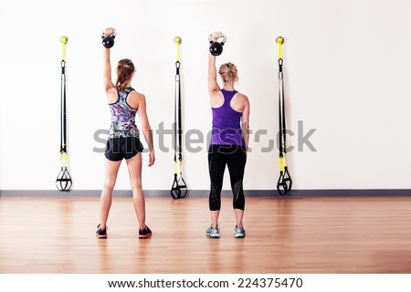 Two young women are doing shoulder presses with kettlebells - stock photo