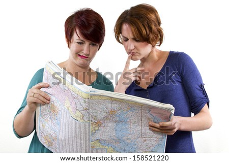 two young women are lost and looking at a map - stock photo