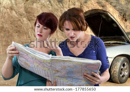 two young women are lost and looking at a map. broken car in the background - stock photo