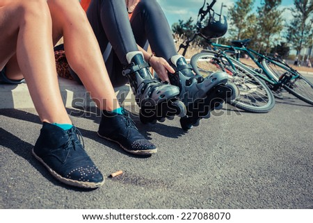 Two young women are sitting by the roadside and one of them is putting on rollerblades - stock photo