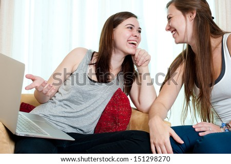 Two young women are sitting, smiling at each other and holding a laptop while indicating. - stock photo