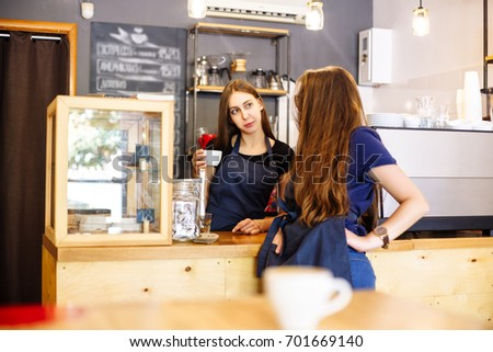 Two young women at a bar counter. Girls barista in aprons and drink espresso in a cafe. Coffee business concept. Small local business