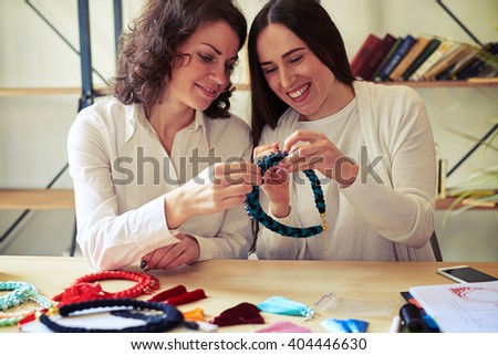 Two young women at the table making jewelry together