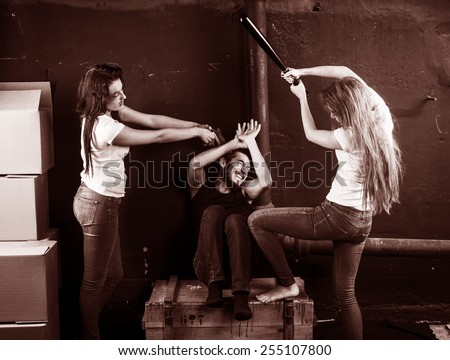 Two young women beaten man sitting on the box in basement on brown background