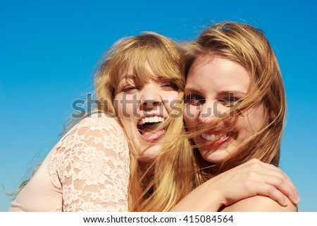 Two young women best friends blonde cheerful girls having fun outdoor against blue sky wind blowing in hair. Summer happiness friendship concept. - stock photo