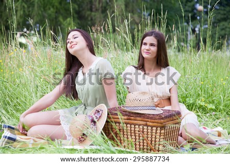 Two young women - best friends having a picnic. - stock photo