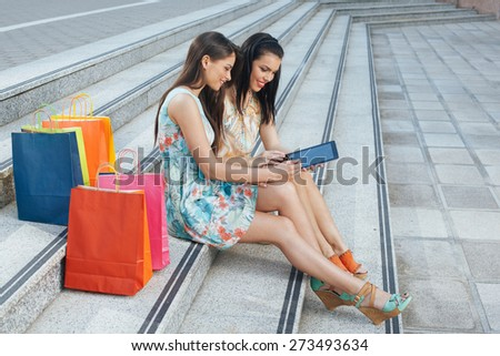 Two young women buying online through a digital tablet - stock photo