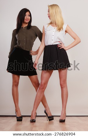 Two young women caucasian and african in trendy short black skirts posing in full length studio portrait on gray - stock photo