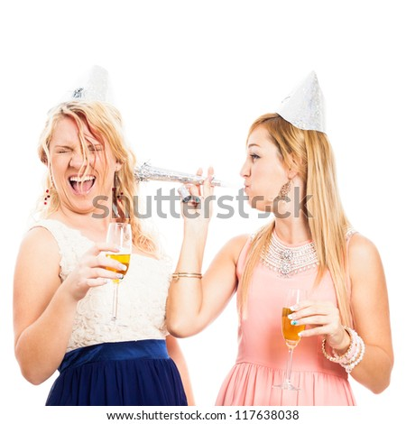 Two young women celebrating with party horn, isolated on white background. - stock photo