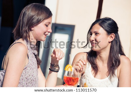 Two Young Women Cheering with Cold Drinks,Italy - stock photo