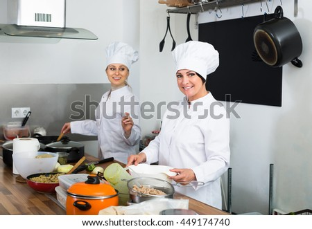 Two young women chefs cooking food at cafe's kitchen - stock photo