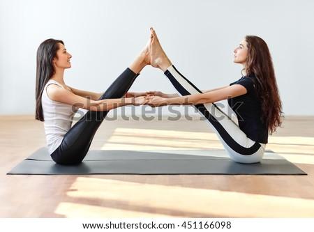 Two young women doing yoga asana buddy boat pose. Paripurna Navasana - stock photo