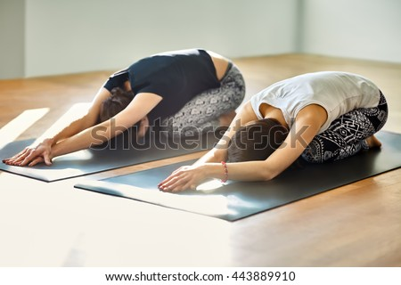 Two young women doing yoga asana child's pose. Utthita Balasana