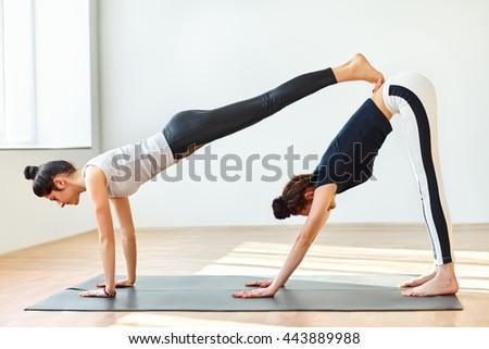 Two young women doing yoga asana double downward dog. Adho mukha svanasana - stock photo